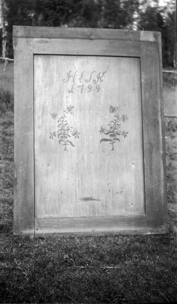Skapdør med «HLSK 1799» malt på.
