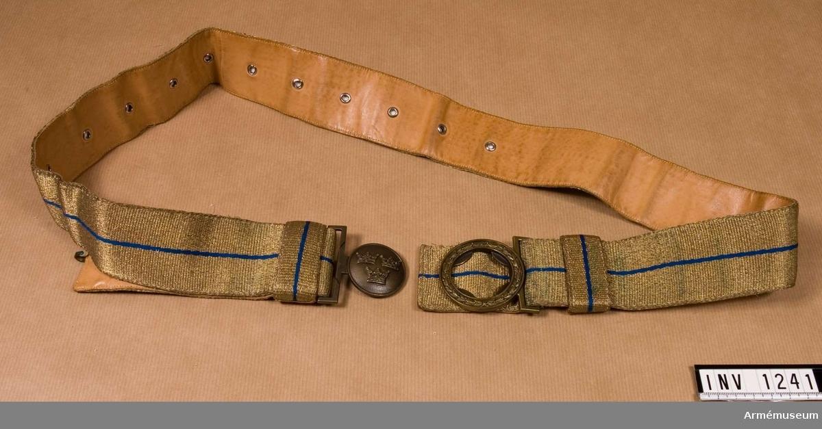 Av bronsfärgad metalltråd och i mitten en blå smal rand. Spännet är i bronsfärgad metall och har en dekor av tre  kronor omgivet av en lagerkrans. Fodrat med ljust läder. Öljetter på ena sidan av spännet för att reglera skärpets längd. På spännets vardera sida två söljor.