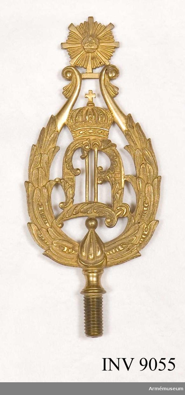 Av förgylld metall med konungens monogram O I omgivet av en  krans, spetsformad. För fastsättning vid fanstången en gängad skruv.  Samhörande nr är 9053-55.