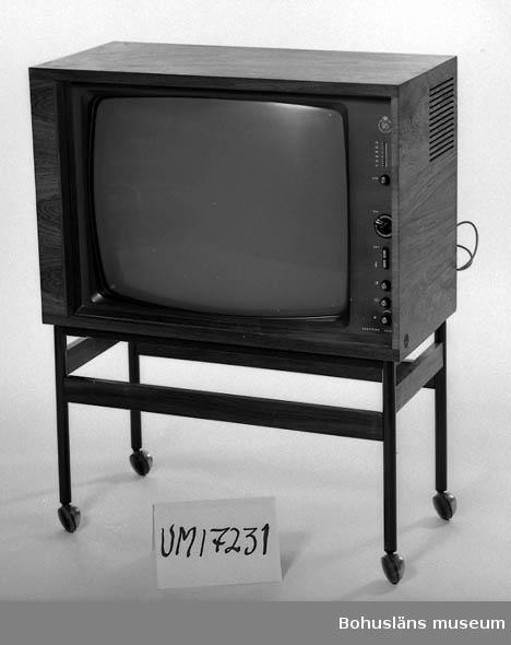 Svartvit tv, modell Beovision 1000. Kanaler: VHF/UHF. Skjutbar lucka för bildröret. Antenkabel och nätsladd. Löst stativ av järn och trä på hjul.
