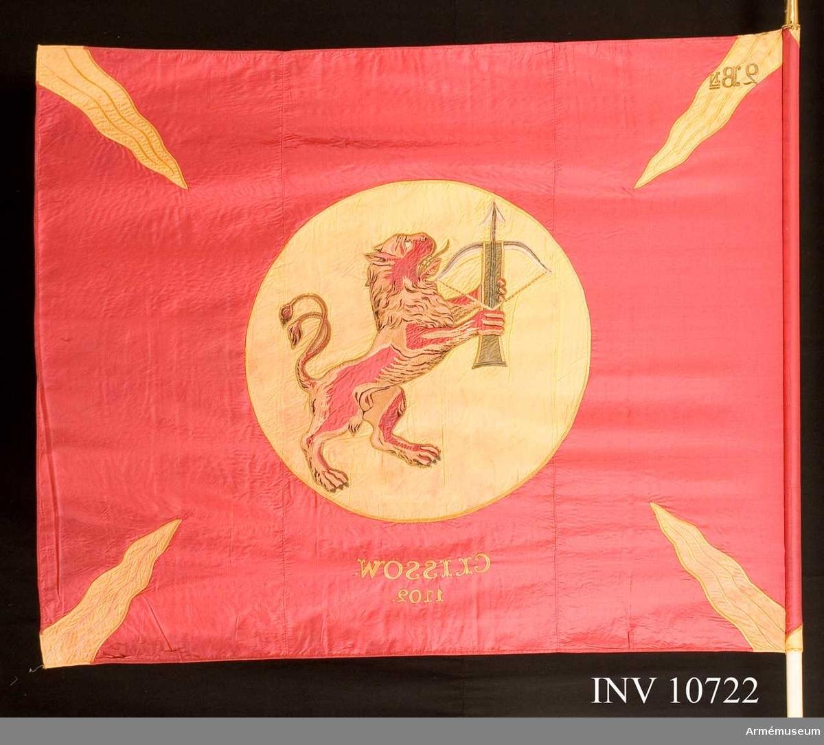 Grupp B.  Utdelad till regementet 1866. Duken är av rött siden med gula flammor i hörnen. På mitten ett gult fält med det uppresta lejonet som i tassarna håller ett uppspännt armborst. Under cirkeln broderat: Clissow 1702.