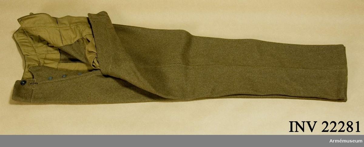 """Grupp C I. Av kakifärgat kläde, långa med två sidofickor. Knapparna är alla av ben i svart färg, 5 st på sprunden och 6 st för hängslen. Baktill finns spänntamp av samma kläde med järn- spänne. LITT  Handbuch der Uniformkunde, Richard Knötel, Hamburg 1937. Sida 136. Belgiska armén har fått sin första kakiuniformer först under första världskriget. Belgiska armén gick i början av kriget i sina brokiga fredsuniformer. Tavla """"Aus dem Uniformwerk"""", Knötel (Jankte) Sieg, Die Solda- ten Europas. Berlin W 63. Belgien stand 1938. Figur 3, 4. Samma byxor ovanpå läderkragar.Enl Granberg 1956."""