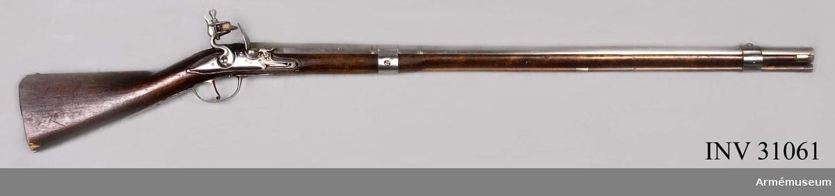 Grupp E II e.  Nominalkaliber 19 mm. Verklig kaliber 18,9 mm. Kammarstyckets längd är 19 cm. Baktill är det åttkantigt och framtill är det på en längd av 5 cm. 16-kantigt. Längst fram begränsas det av en insvarvad och en upphöjd rand. Ungefär 6,8 cm framför sistnämnda rand gå kring det runda långa fältet ett par insvarvade och en upphöjd rand. På svansskruvsstjärten sitter ett långt ståndsikte. På kammarstyckets översida finns en kronstämpel med ett monogram av bokstäverna INB, samt längre ned siffran 2. På undersidan är jönköpings ring inslagen. Pipan har 2 häften och korsskruven går uppifrån.  Låset har ej varhake. Blecket är kullrigt och går baktill ut i en spets. Hanhalsen är baktill kullrigt eller avrundad och läppskruvshuvudet är päronformigt samt har skåra. Fängpannefotenär lång med hål för den bakre låsskruven. Pannskruven för eldstålsfjädern går utifrån. Eldstålsfjädern bukt går bakom hålet för den främre låsskuven. På bleckets yttersida under fängpannan finns en kronstämpel och samma stämpel med bokstäverna I N B i monogram som på pipan.  Stocken är av björk och svart. Kolvryggen är plan. I piprännans botten är årtalet 1705 samt ett monogram av bokstäverna NB inristat. På kolvens bakände är en bokstav, sannolikt N inlagen. En liten bit trä utslagen. En liten bit trä urslagen från kolvtån.  Järnplåtsbeslagen består av en kort bakplåt, som fasthålles av stift och som blott betecker hälen samt den övre hälften av kolvens bakände, rätt långt avtryckarebleck, som baktill fasthålles av en nit, framtill av den uppifrån kommande korssruven, platt S-formigt sidbleck, två band, av vilka det bakre, 3 cm breda sitter 20 cm. framför bakre pipänden, men den främre, som är 2,9 cm brett. går kring pipa och framstock 8,1 cm. bakom pipmynningen. en slät mellanrörka och 1,8 cm brett näsbleck, som sitter 1 cm bakom framstockens främre ände. Det främre bandet har på översidan ett båtformigt korn och fasthålles av ett stift, det bakre har på vnstra siden en urtagning för karbin