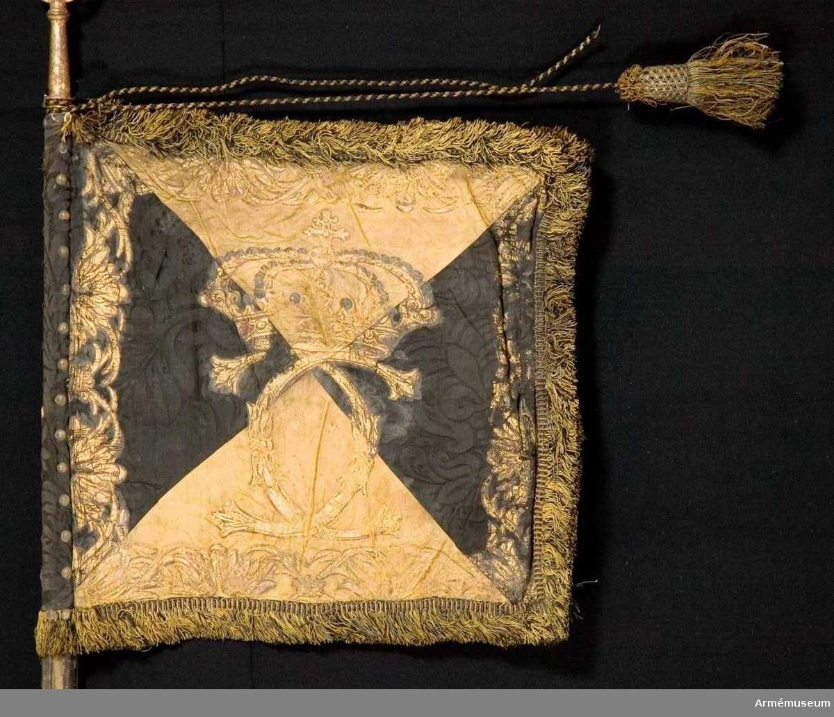 Duk: Tillverkad av dubbel sidendamast, fyrstyckad i gult och svart. Fodrad med grov lärft. Duken fäst med tre rader tennlikor runt stången. Obs! dock ej på några band.  Dekor: Målad på utsidan upprätt lejon, nedre halvan svart (på den svarta duken grå), den övre i brunskuggat guld, följt av två gyllene sexuddiga stjärnor (Västergötlands vapen); bårder längs kanten av stiliserade bladverk, kronor och palmkvistar.  På inre sidan i brunskuggat guld rikt ett dubbelt C krönt av sluten, stor krona med pärlor i silver och stenari rätt och grönt; bården längs kanten lik yttre sidans.  Frans: Dubbel, tillverkad av svart och gult silke, metalltråd.   Stång:  Tillverkad av trä, kanellerad, dovt grönmålad; löpande bärring; nedanför greppet en extra förlängning; holk och spets av förgylld mässing, spetsen med dubbelt C krönt av en öppan krona.  Banderoller av svart och gult silke, endast en tofs kvar.