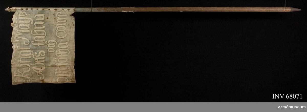 Duk: Tillverkad av dubbel, blå lärft, vikt i nedre kanten. Sydd i övre och sidkanten. Duken fäst vid stången med tennlickor av järn på vitt band.  Dekor:  Målad på insidan sluten krona i gult med röda skuggor, pärlor i vitt och stenar i rött. Kronan omgiven av C R S i vitt med svart kant. På yttre sidan text i vitt på fyra rader.  Stång av trä, blåmålad. Klack av järn, liten holk av tenn.