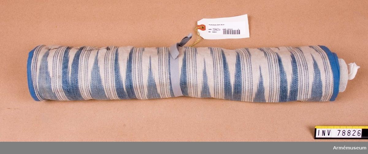 Grupp I:IV.  Tyget är av linne med flamfärgat inslag i viggmärken.  Ett märke efter den ursprungliga monteringen synes tydligt. Handbandet är nymonterat.