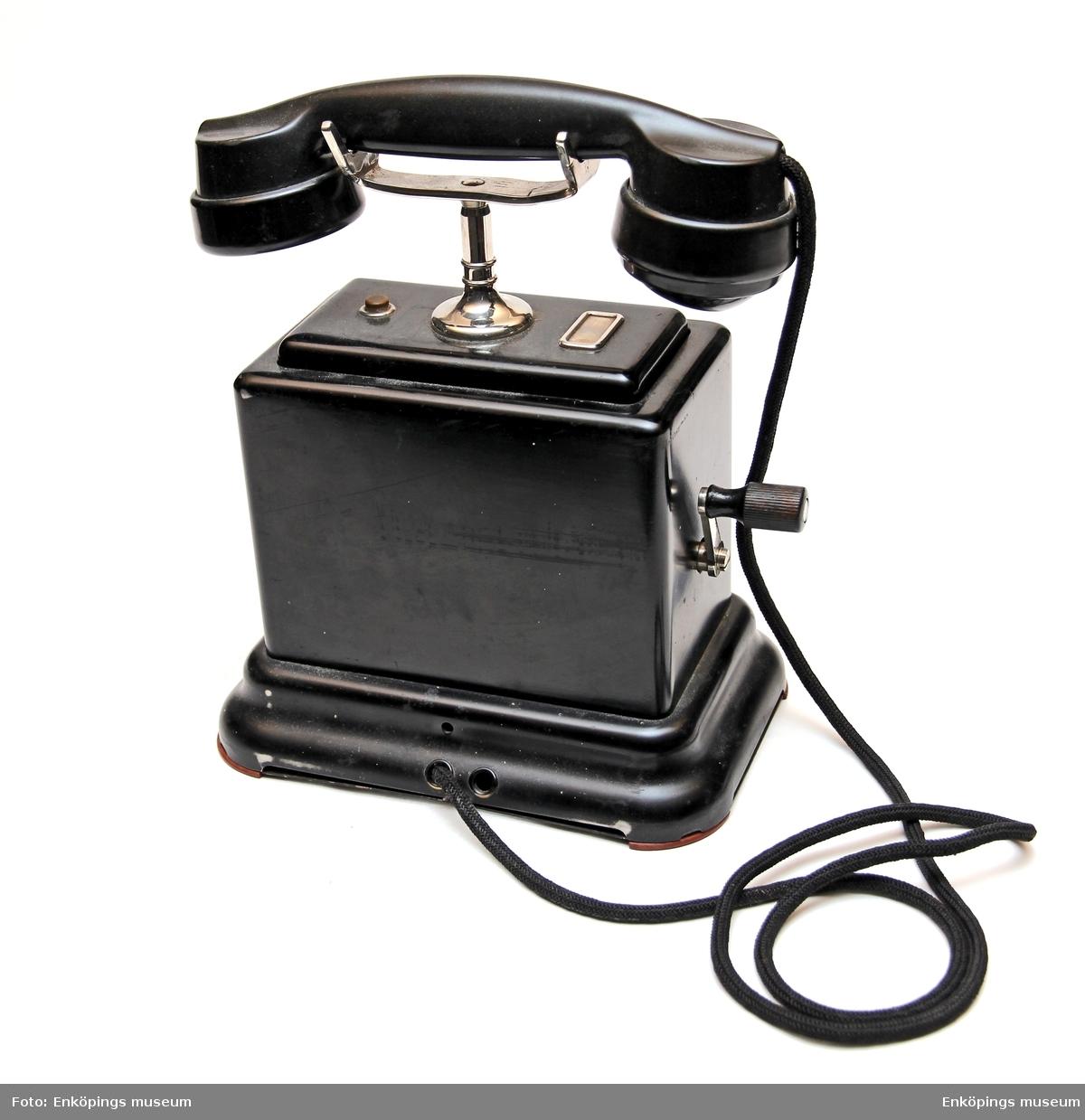 Vevtelefon med vev på ena sidan. På telefonens undersida är den märkt AB100 Schema A   K.T.V.1941.