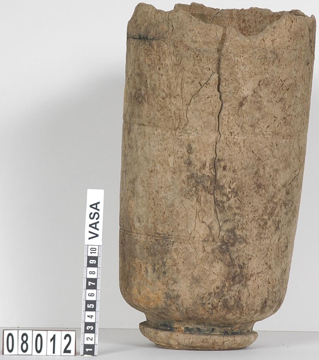 En svarvad träflaska med lock. Flaskan har en kort hals, sluttande skuldror och skrånande sidor. Runt flaskans kropp löper dekorativa, svarvade ringar. Flaskans saknar botten och två mindre delar av flaskan är bortbrutna.