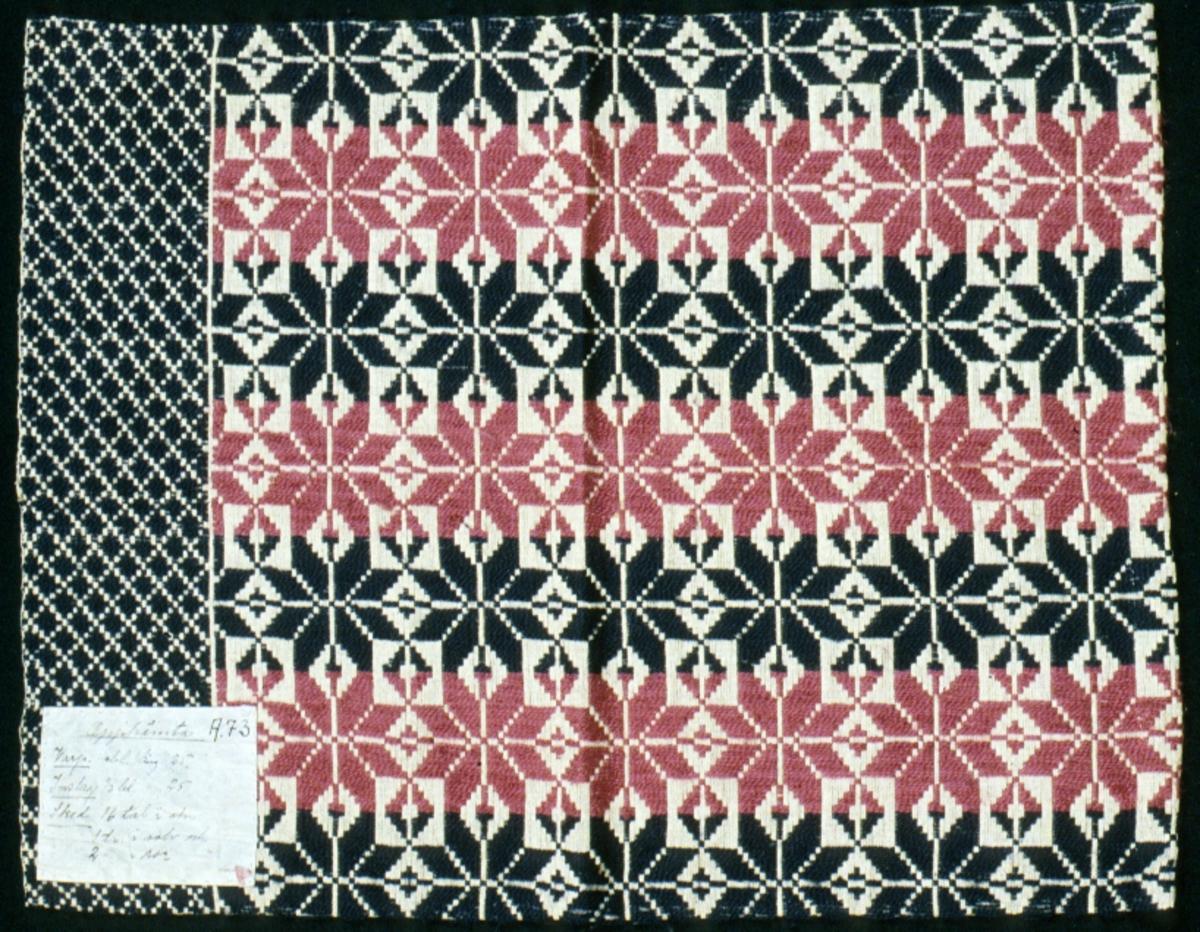 """Vävprov i opphämta. Stjärnbårder i rosa och mörkblått, 60 mm breda, på ljus botten. Ett 85 mm brett bårdparti i ena kortsidan i blått med diagonalt rutverk. Fållad i tre sidor, stadkant i sidan med bården. Varp i oblekt lingarn nr 25, 17 trådar/cm. Botteninslag i halvblekt lingarn nr 25, 16 inslag/cm.Mönsterinslag i 2-trådigt s-tvinnat ullgarn, 7 inslag/cm. Två botteninslag mellan varje mönsterinslag.Märkt på framsidan med påsydd lapp med texten:""""Opphämta  A.73 Varp. obl. ling. 25 Inslag 1/2 bl. ling. 25Sked 16 tal i aln1 tr. i solv och2 tr. i rör""""."""