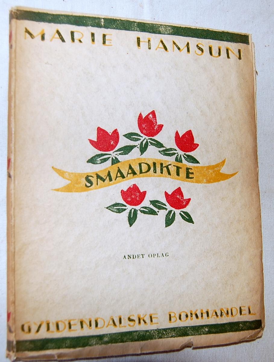 På bokens forside: Et slynget bånd omgitt av 5 røde blomster
