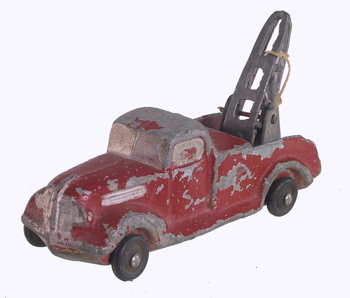 Form: Lekebil formet som lastebil med heisekran. Støpt i et stykke, med løse hjul festet på stift foran og bak, og svingbar heisekran festet til lasteplanet.