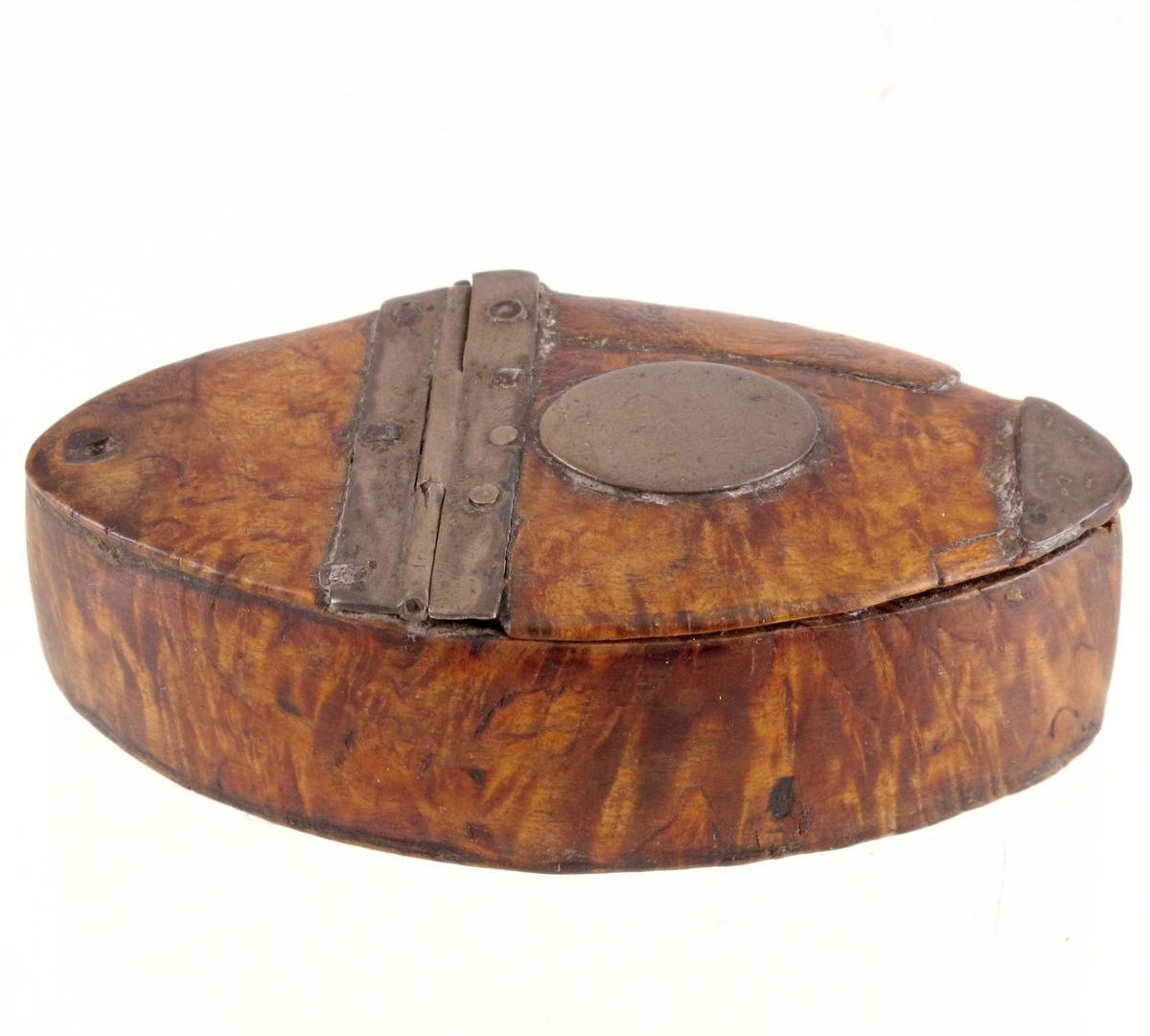 Liten ask med ellipseform, vippelokk løst, har vært festet. Beslag og små detaljer av metall
