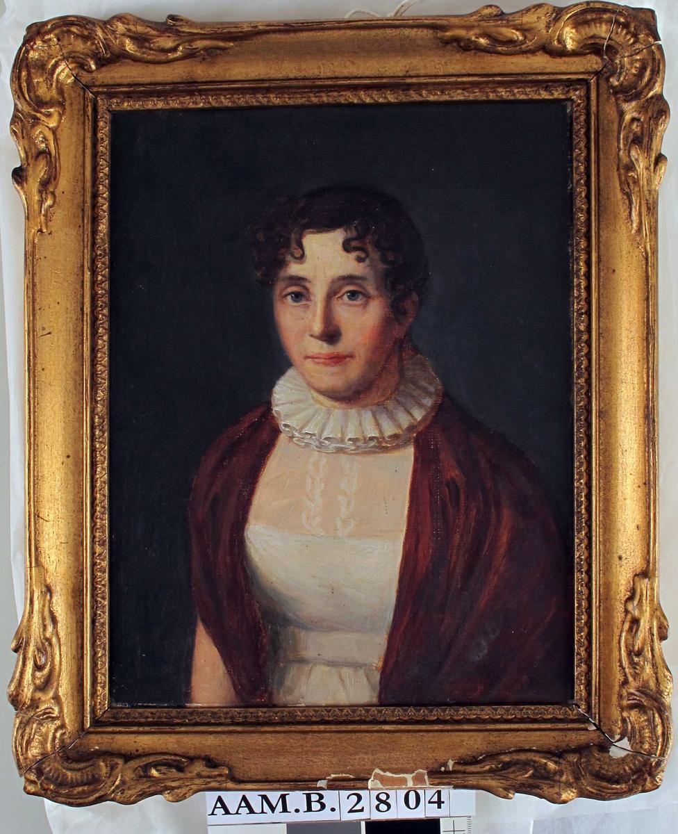 """Portrett, middelaldrende kvinne. Brystbilde. Kledd i hvit bluse med rød kappe, evnt. sjal e.l. """"Pipekrage"""" om halsen. Personen er ukjent, men står giveren nær i slektskap."""