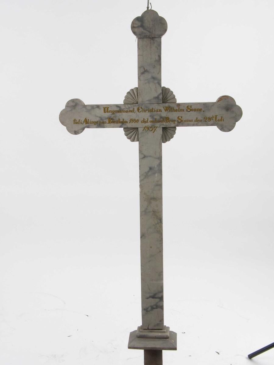 Kors i tre, malt lyst grått med marmorering og innskrift.