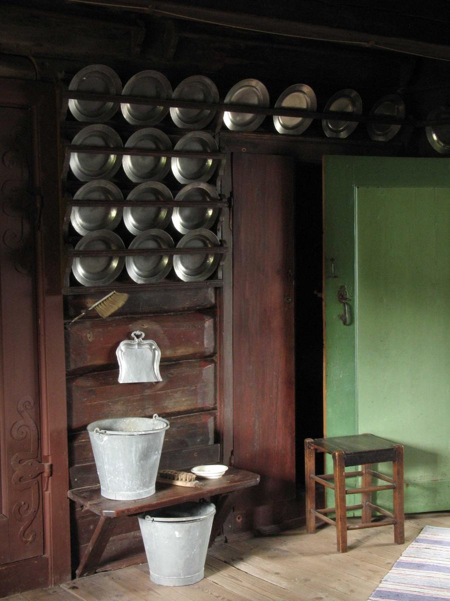 Merdøgaard. Interiør kjøkkenet. Tinntallerkner i rekker på brunmalt vegg, grønnmalt dør. Skurebøtter, taburett.
