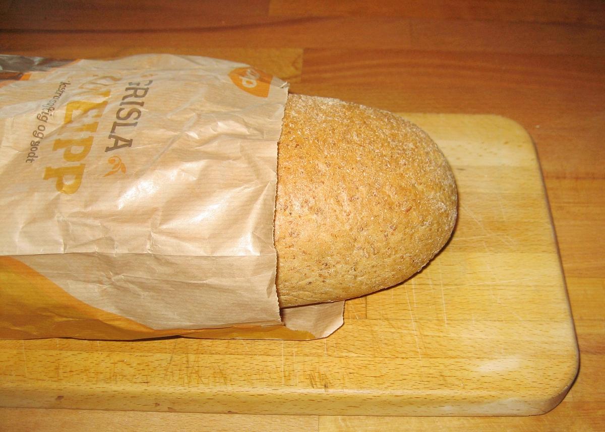 Motivet på brødposen er to brød som ligger på en fjøl. Det er et rutete stykke stoff i bakgrunnen. Motivet er i brune nuanser.