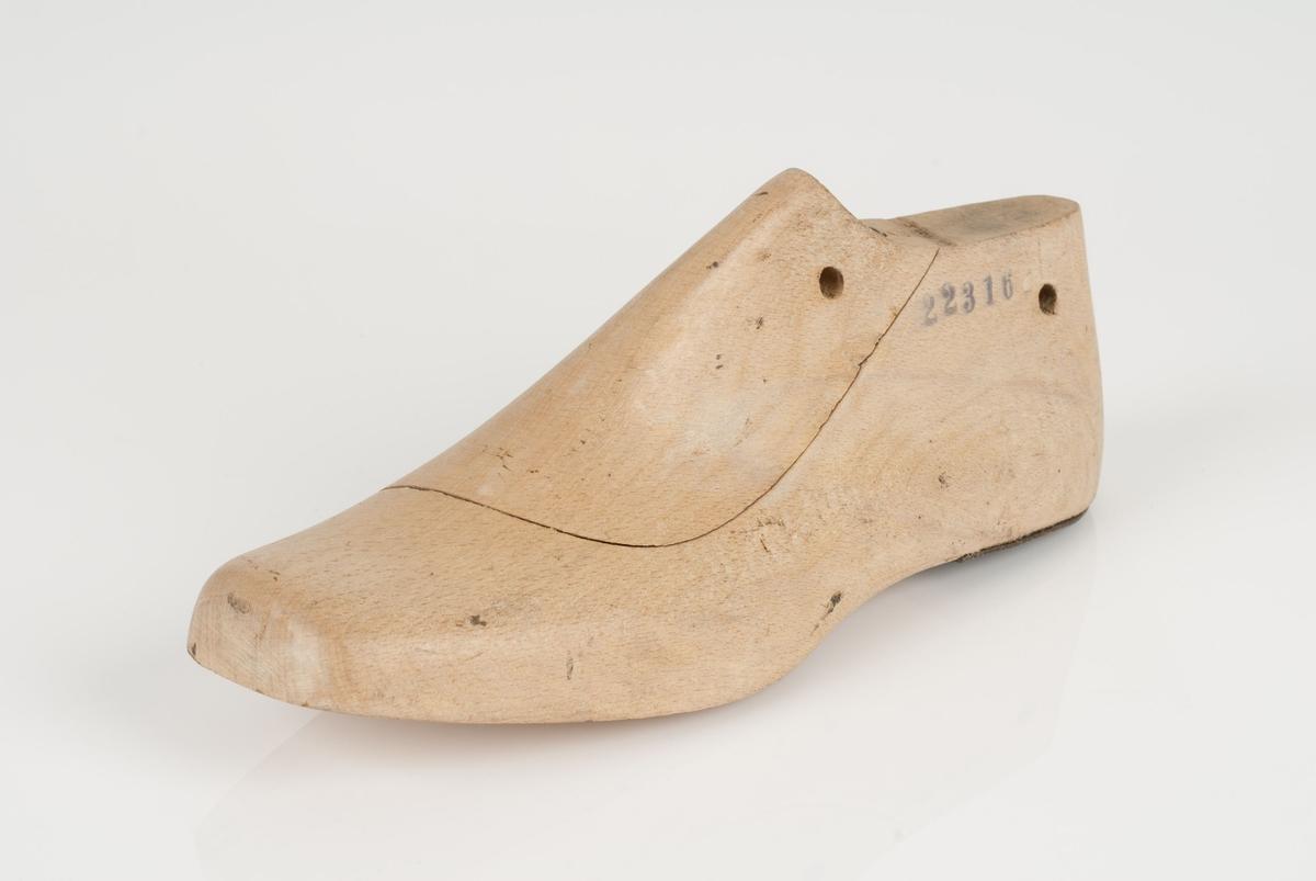 En tremodell i to deler; lest og opplest/overlest (kile). Venstrefot i skostørrelse 39, og 9 cm i vidde. Hælstykket av metall.
