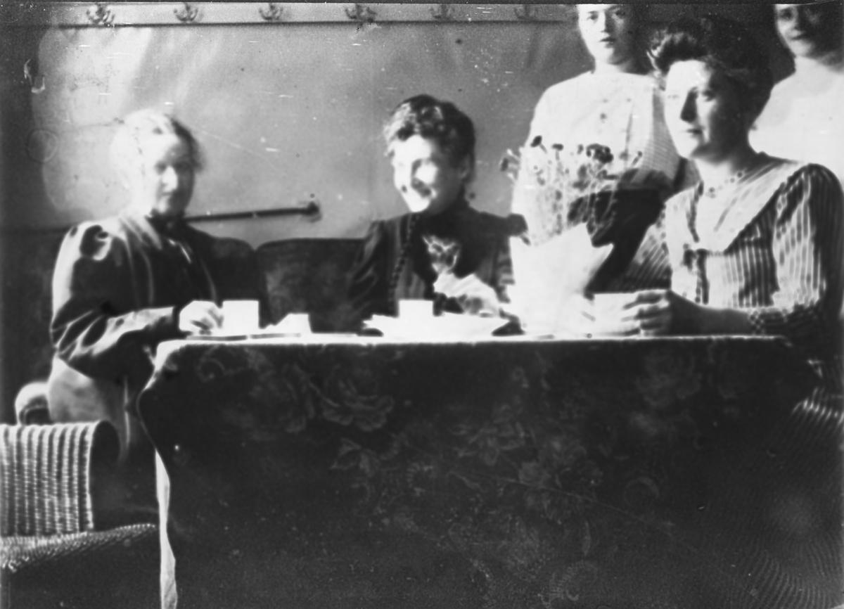 Hjemmenes Vels kjøkken. Kvinner drikker kaffe ved pent oppdekket bord.