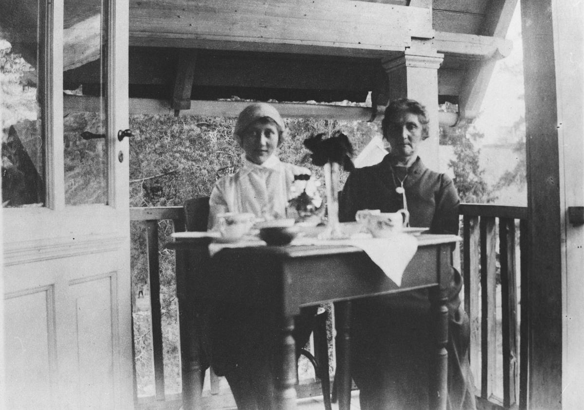 To kvinner sittende ved bord på veranda. Kafeen i Bergersbakken