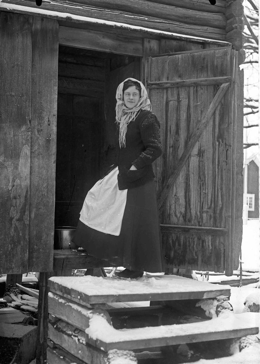 Kvinne som står i døra til stabburet.