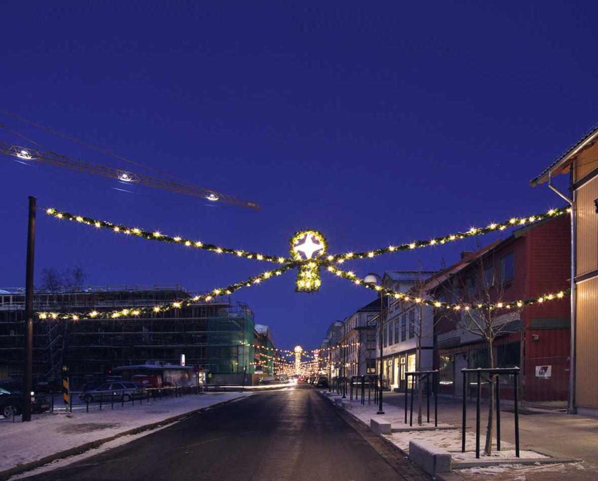 Julebelysning.  Julegata i Lillestrøm. Granbar med hvit julebelysning og midtdekorasjon hengende slik at belysningen danner allèeffekt
