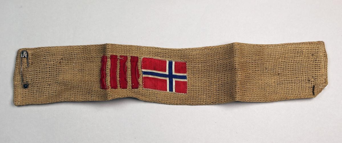 Norsk flagg og fire røde render er sydd på