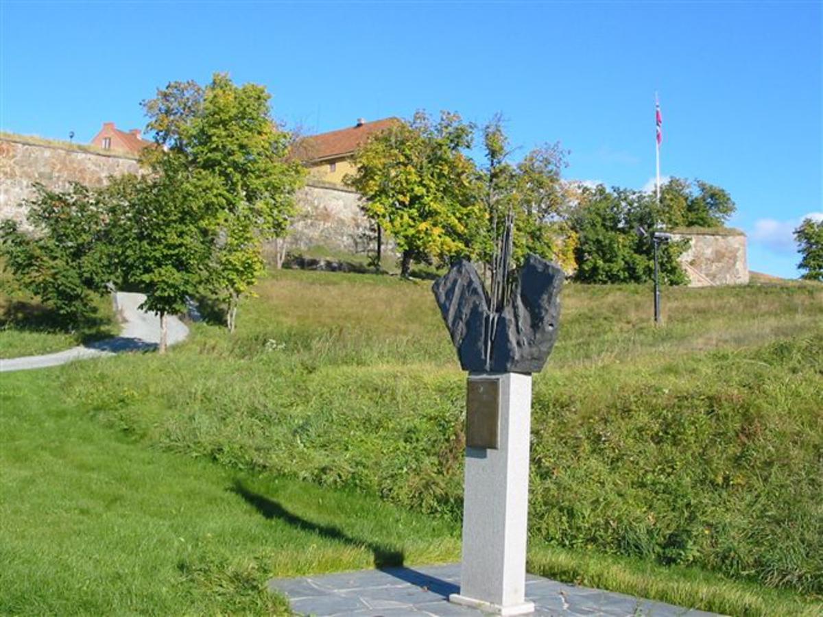 Granittsøyle med kopperplate (m/inskripsjon) hvilende på en sokkelplate med flomlys. På toppen selve monumentet som består av to vinger av stein i V-form, og i midten 21 aks (uten korn) som vokser ut av steinen. Symboliserer de to stridende parter og de 21 falne FN-soldatene.