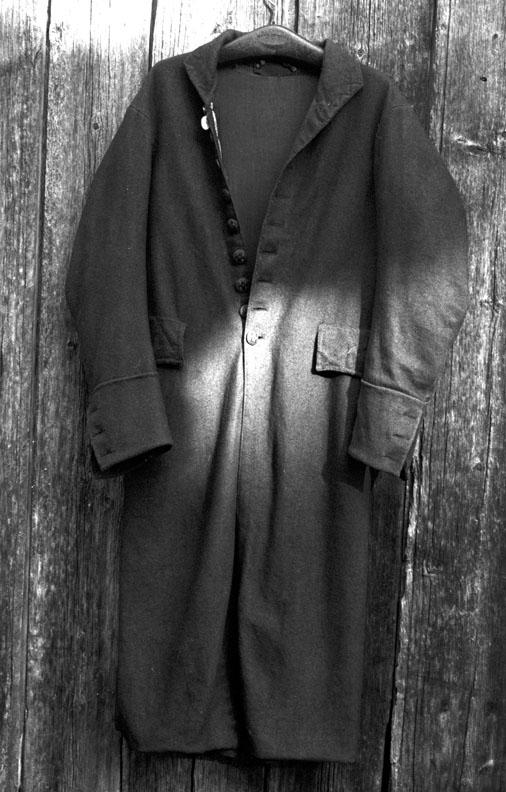 Lang frakk med sid kappe nede, som har splitt bak opp til ryggen og med folder som på innsida holdes sammen av påsydde stoffhemper. Knepping i front med plastknapper (oppført i protokoll med trukne knapper, men stoff ikke synlig/kjennbart nå. Muligens nedslitt). To lommer i front.