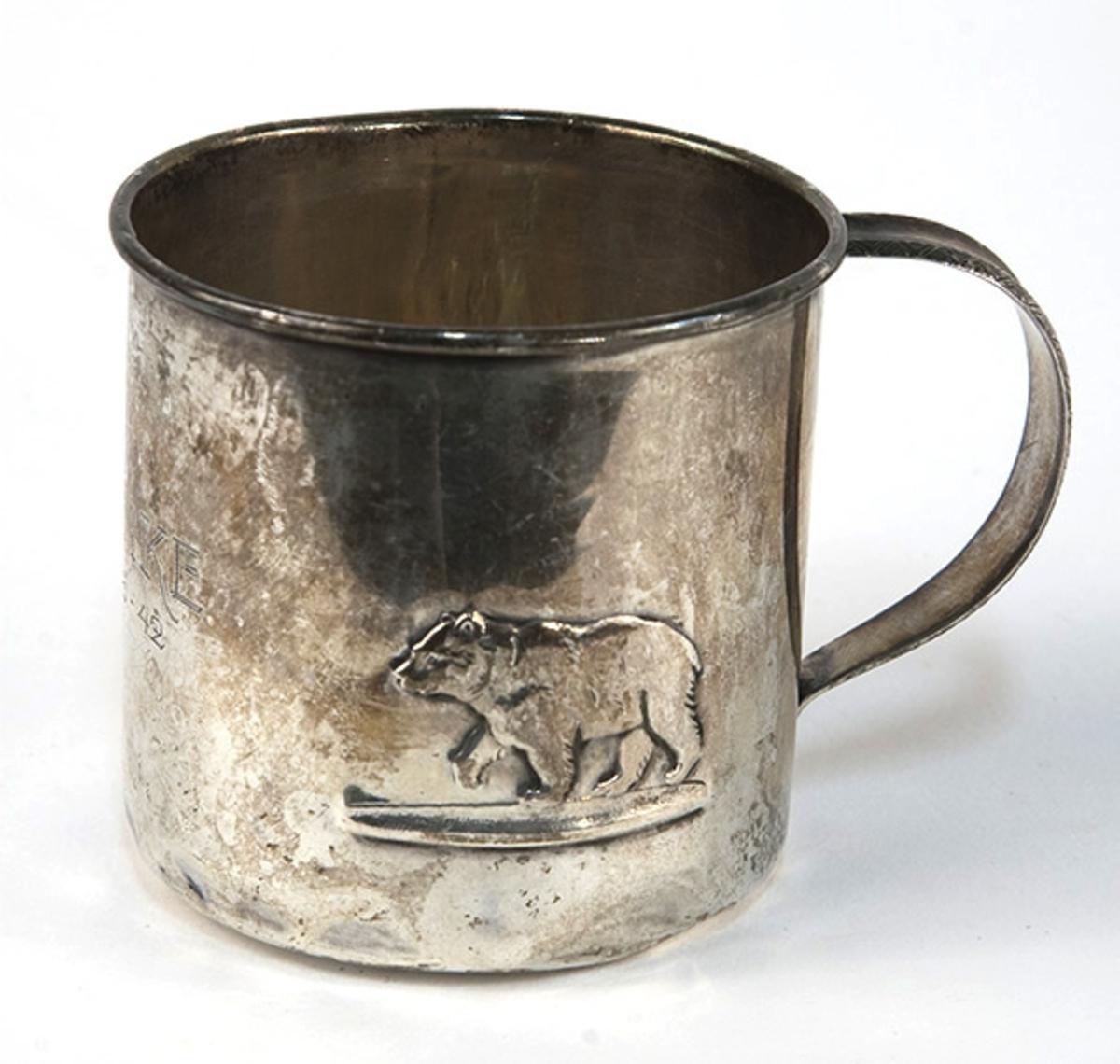 Dåpskrus. Dyrefigurer på siden. Gravert tekst Venke 17-5-42. Sølv eller sølvplett. To utydelige stempler.